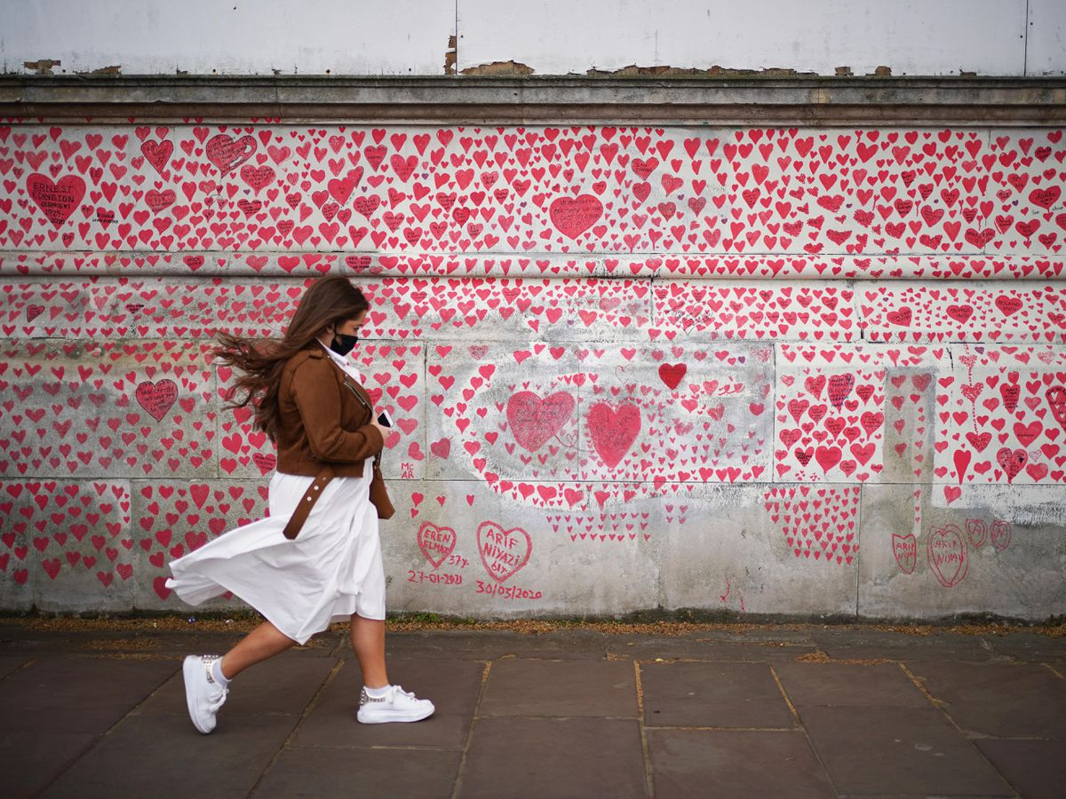 A woman walks past the National Covid Memorial Wall