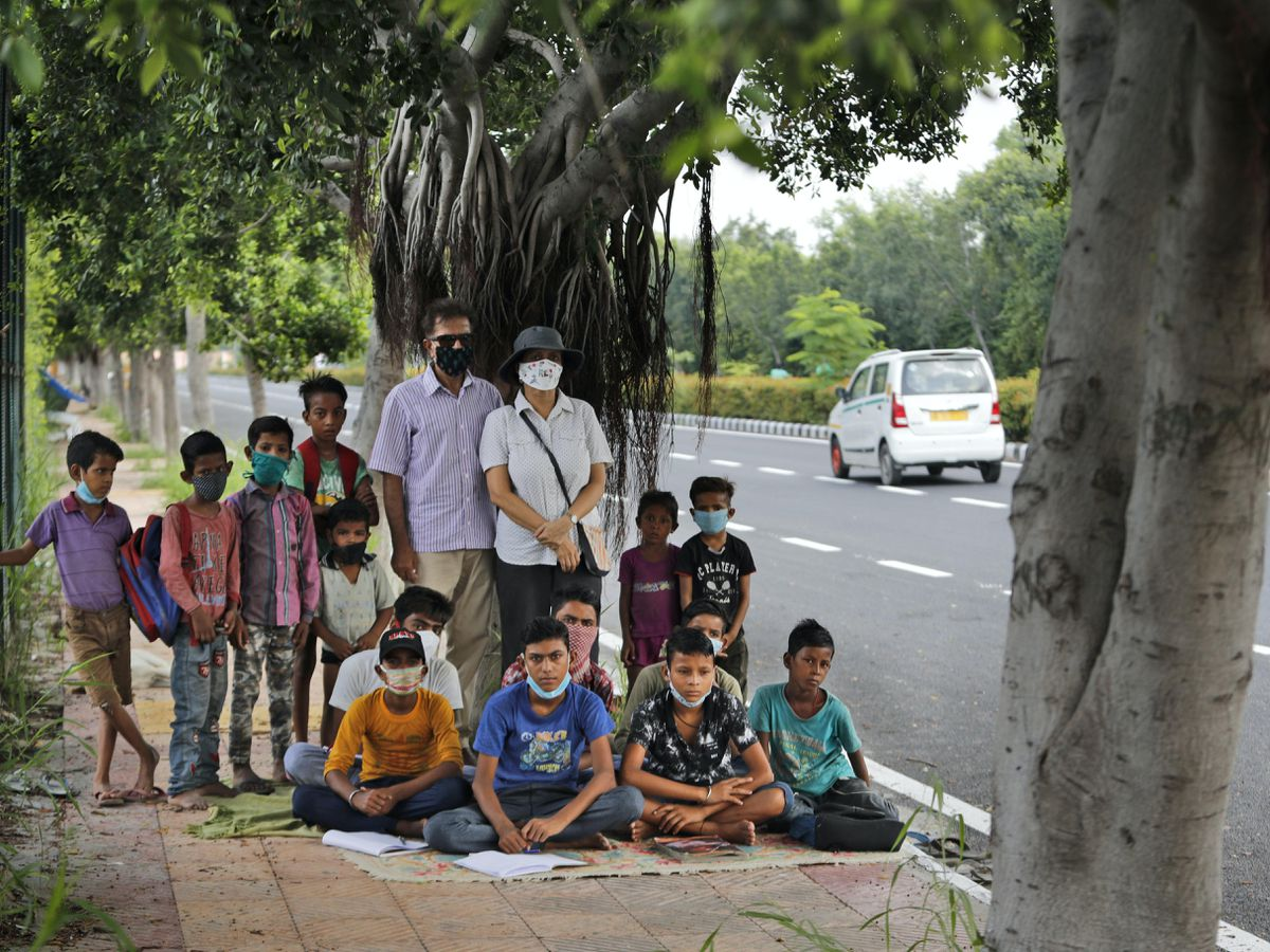 Former diplomat Virendra Gupta and his singer wife Veena Gupta with children who they teach on a pavement in New Delhi, India