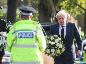 Prime Minister Boris Johnson carries flowers