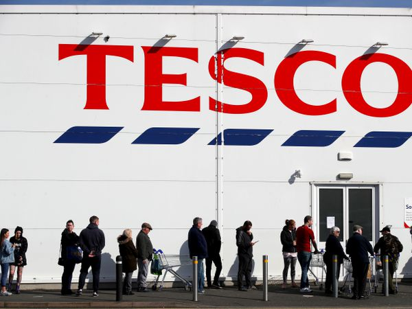People queue outside a Tesco Extra store