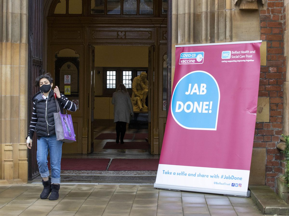 A woman walks past a Covid-19 sign at Queen's University, Belfast (Liam McBurney/PA)
