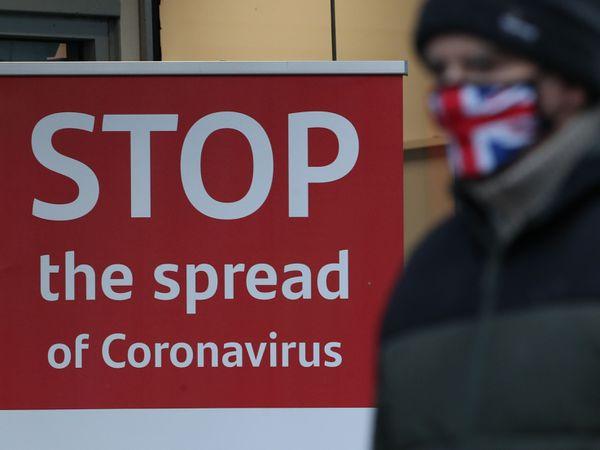 A man wearing a face mask walks past a coronavirus advice sign