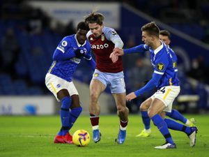 """Aston Villa's Jack Grealish tries to squeeze between Brighton and Hove Albion's Joel Veltman (right) and Yves Bissouma (left) during the Premier League match at the AMEX Stadium, Brighton. Picture date: Saturday February 13, 2021. PA Photo. See PA story SOCCER Brighton. Photo credit should read: Ian Walton/PA Wire. RESTRICTIONS: EDITORIAL USE ONLY No use with unauthorised audio, video, data, fixture lists, club/league logos or """"live"""" services. Online in-match use limited to 120 images, no video emulation. No use in betting, games or single club/league/player publications."""