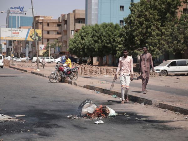 People walk on a street in Khartoum, Sudan, two days after a military coup