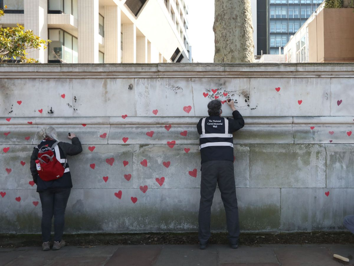 Members of bereaved families paint red hearts on the Covid-19 Memorial Wall