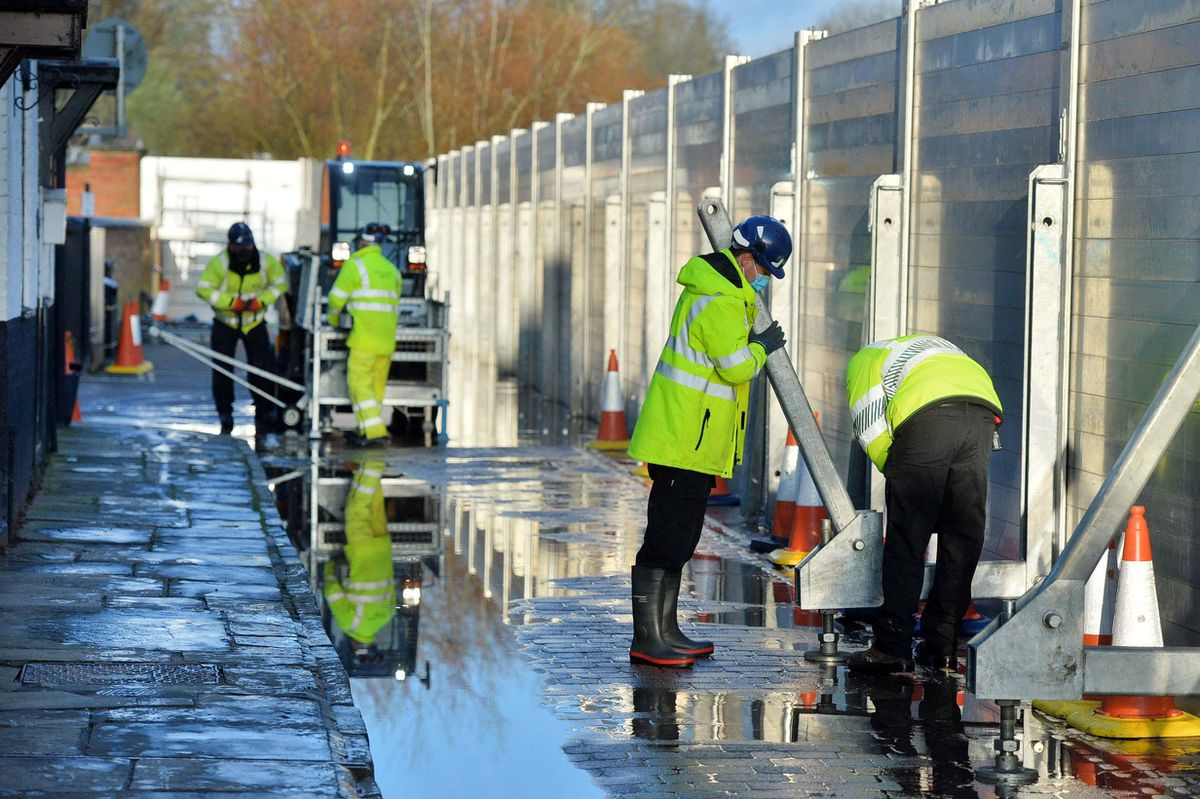 Environment Agency workers examine the flood barriers in Bewdley
