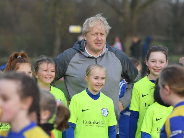 Prime Minister Boris Johnson before a football match stands with a group of junior players