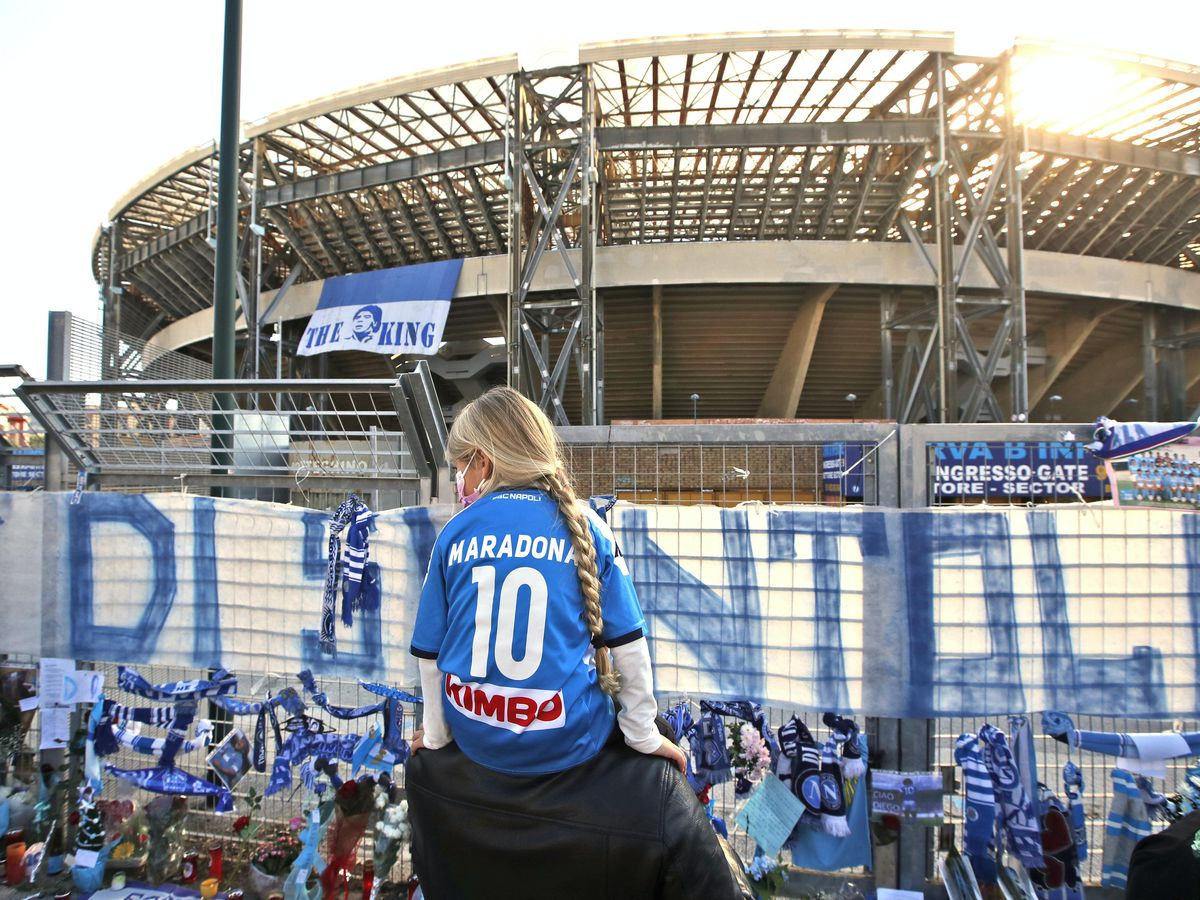 A girl wearing a Maradona number 10 shirt looks at the tributes at Napoli's San Paolo Stadium