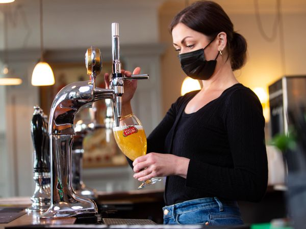 Woman pulling pint in pub