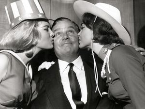 Holiday Camp 'King' Billy Butlin receiving a dual liss from two Miss World contestants