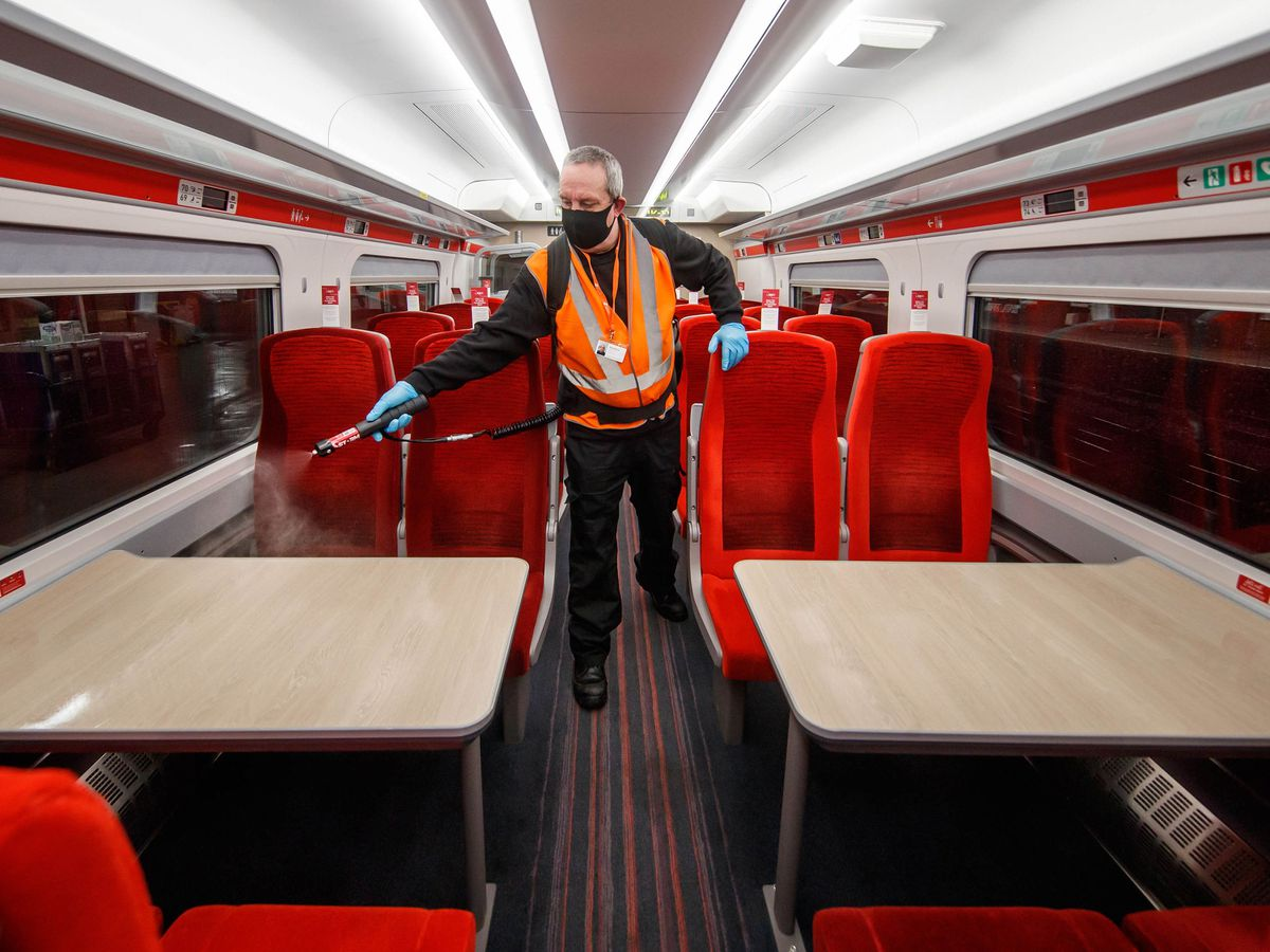 A worker cleaning a train