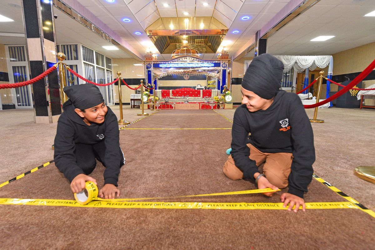 Pictured laying tape down in the prayer room, to enable social distancing, are Ruben Johal and Gurmukh Benning, both aged 12