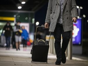 A man pulling a suitcase on wheels