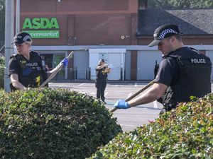 Police officers searching the car park at Asda after a man was stabbed. Photo: SnapperSK