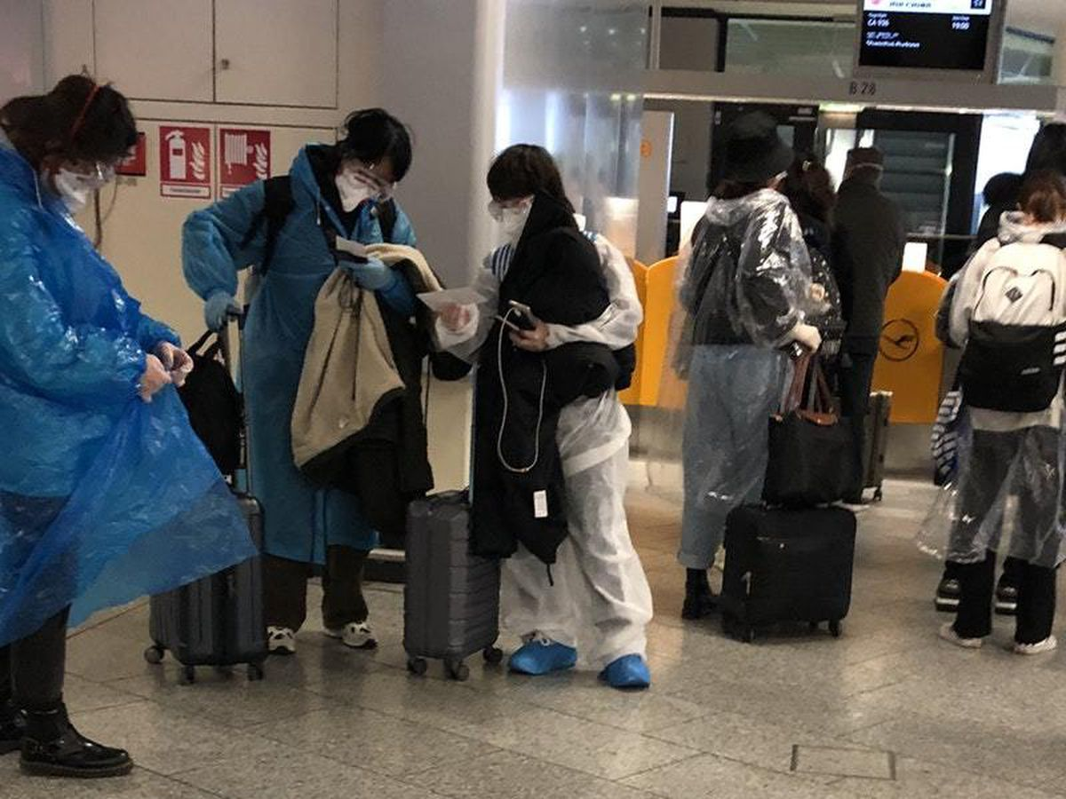 Passengers makeshift hazmat suits at an airport in Shanghai