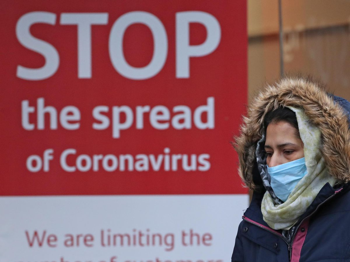 A woman walks past a coronavirus sign in Glasgow
