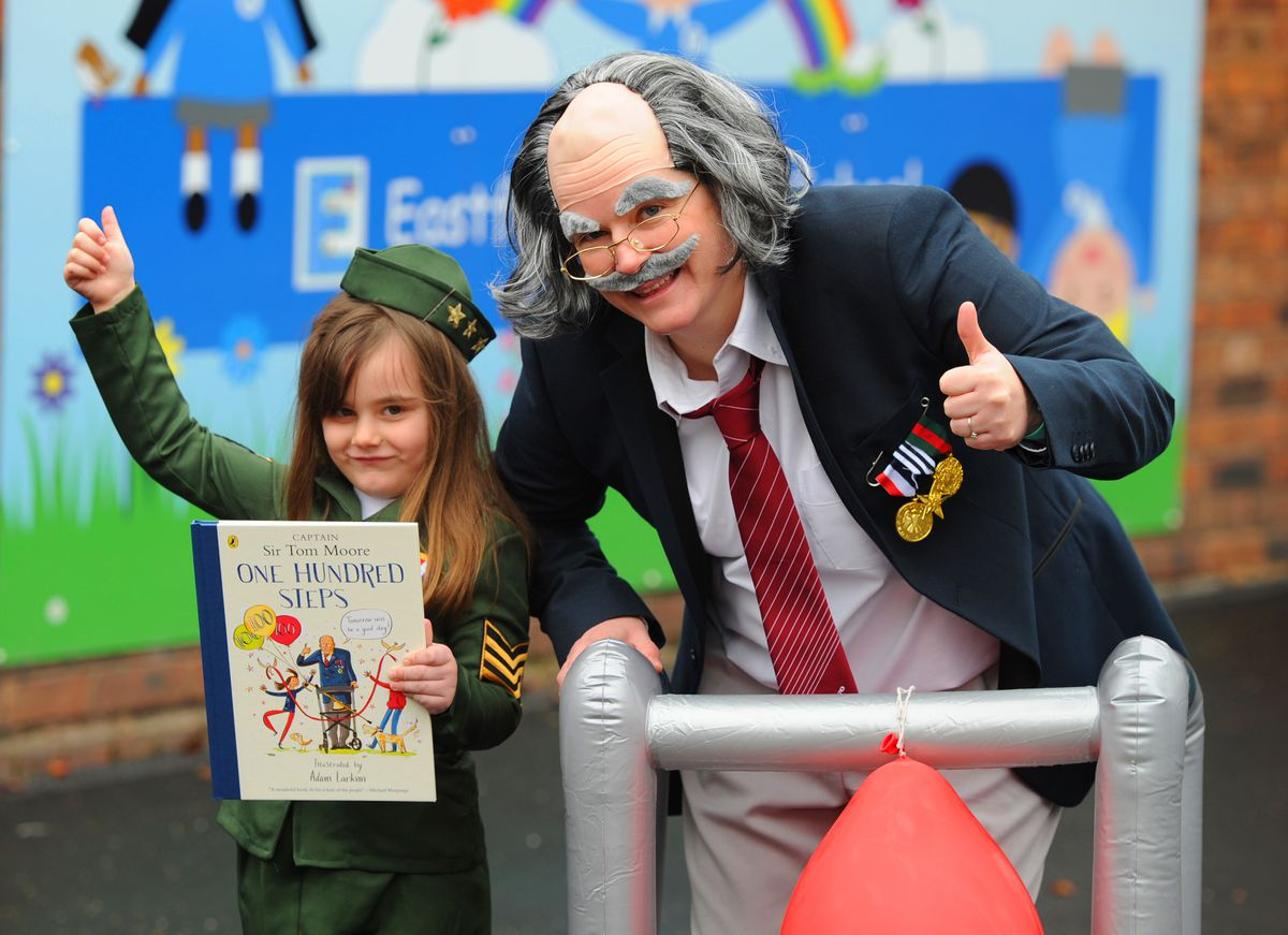 English leader Cathy Lea, dressed as Captain Sir Tom Moore, hands over a copy of One Hundred Steps to Lily Rothans, aged five