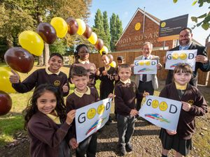 Pupils at Holy Rosary Catholic Primary Academy celebrate being awarding 'Good' Status in their Ofsted Inspection with (centre, back) Councillor Dr Michael Hardacre, the City of Wolverhampton Council's Cabinet Member for Education and Skills and Principal, Adam Jewkes.