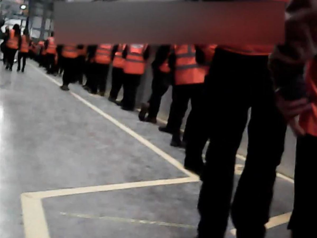 The footage shows workers lined up