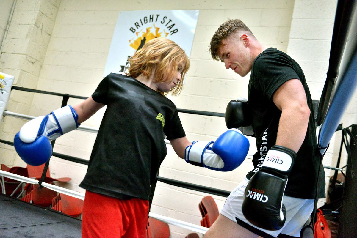 Coach Sam Hinett working with seven-year-old Lewis Hedges at Brightstar Boxing in Shifnal