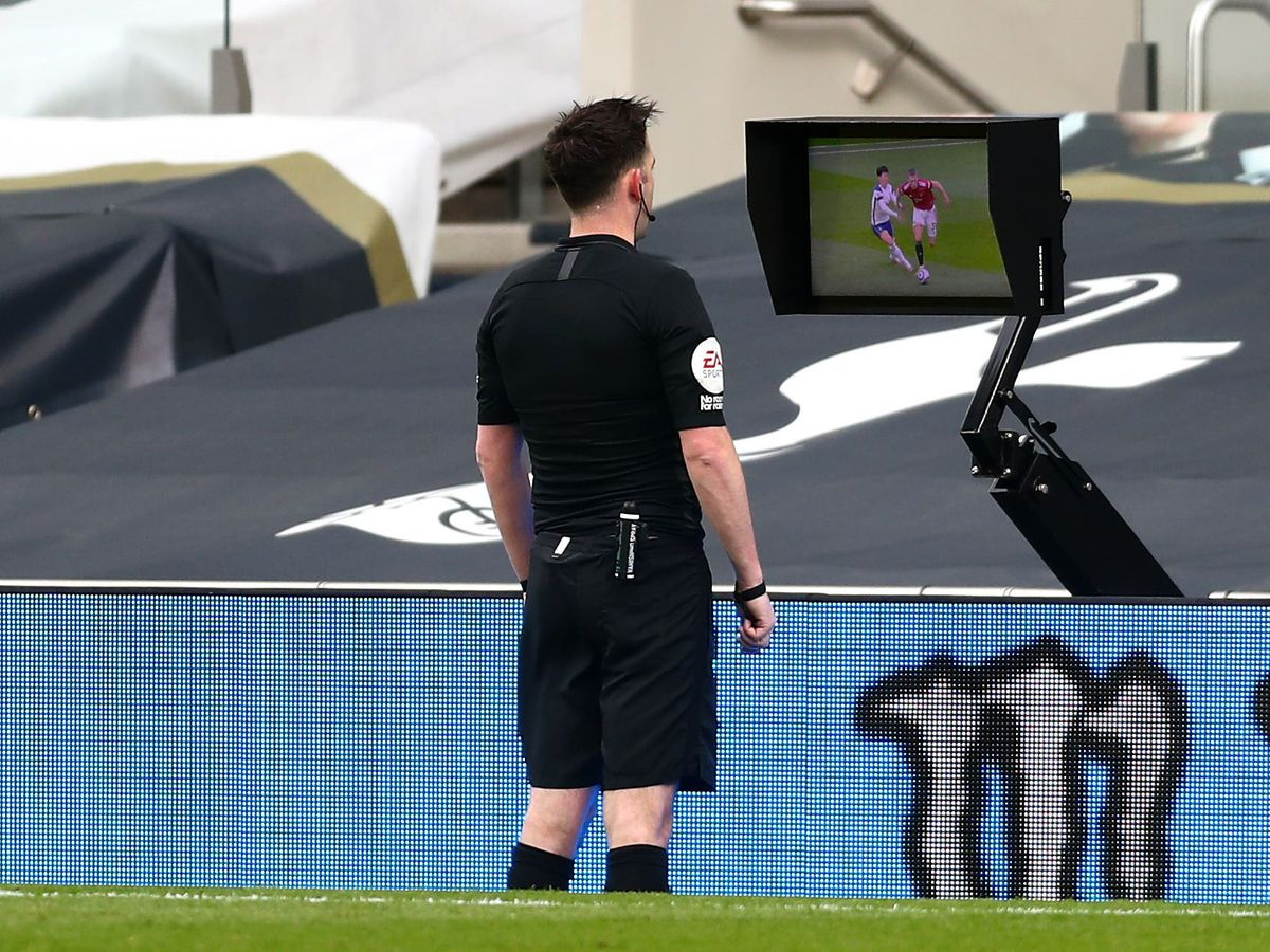 Referee Chris Kavanagh consults the pitchside monitor before ruling out Edinson Cavani's goal