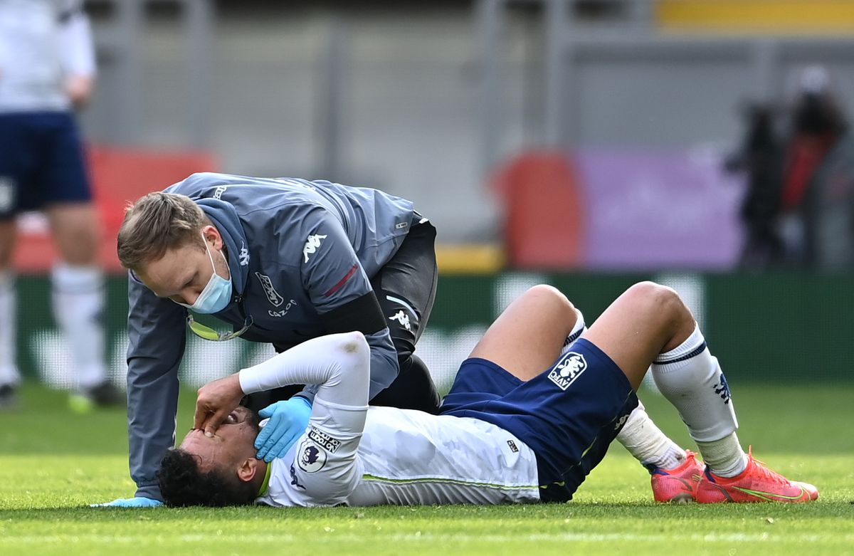 Aston Villa's Trezeguet receives treatment for an injury during the Premier League match at Anfield