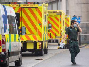 A paramedic walks past a line of ambulances