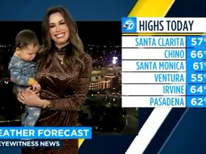 Leslie Lopez holds her son while giving a weather report for ABC7