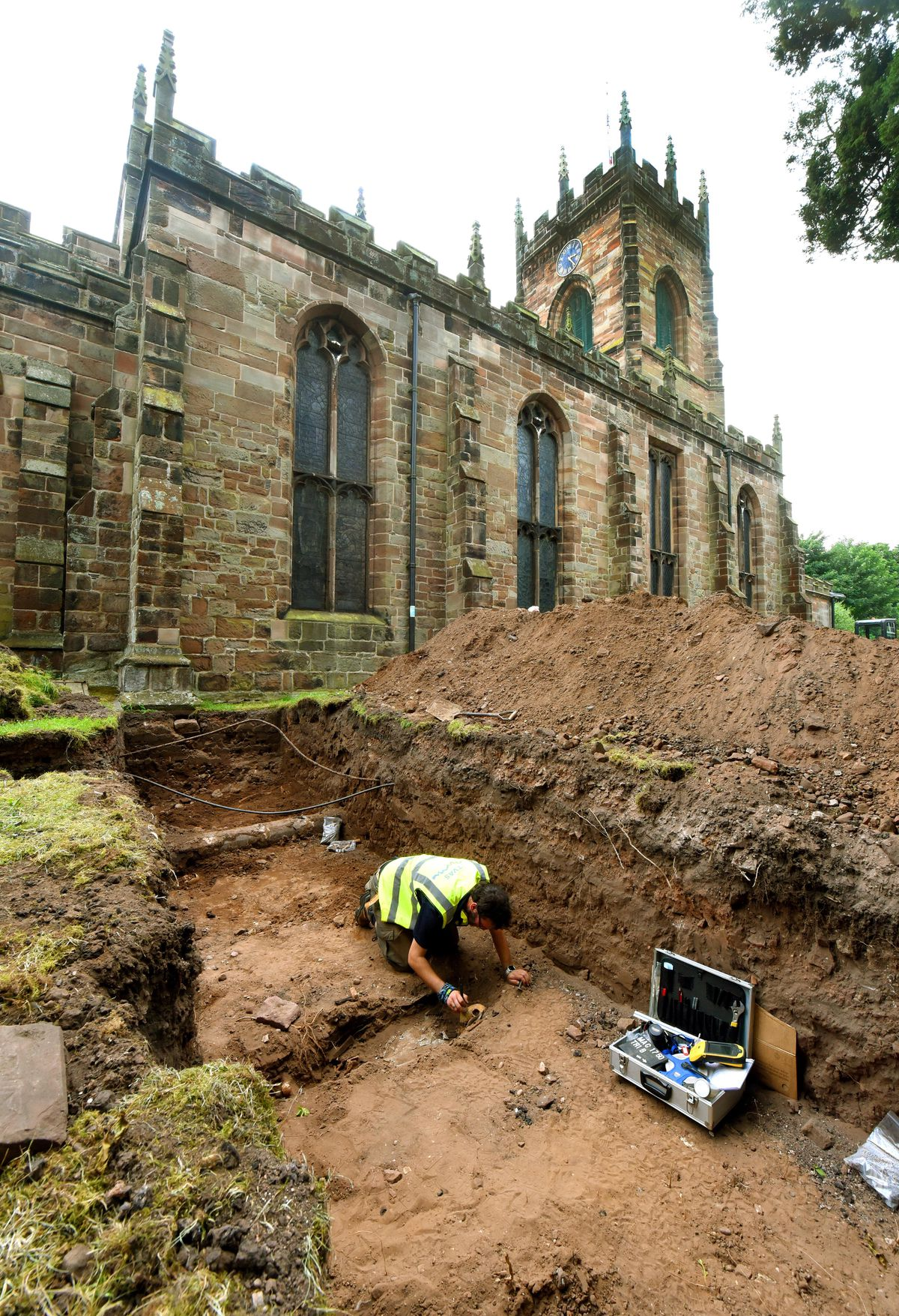 Archaeology dig at St Michael's and All Angels Church, Penkridge. Archaeologist Garreth Davey at work on one of the discovered skeletons in the trench