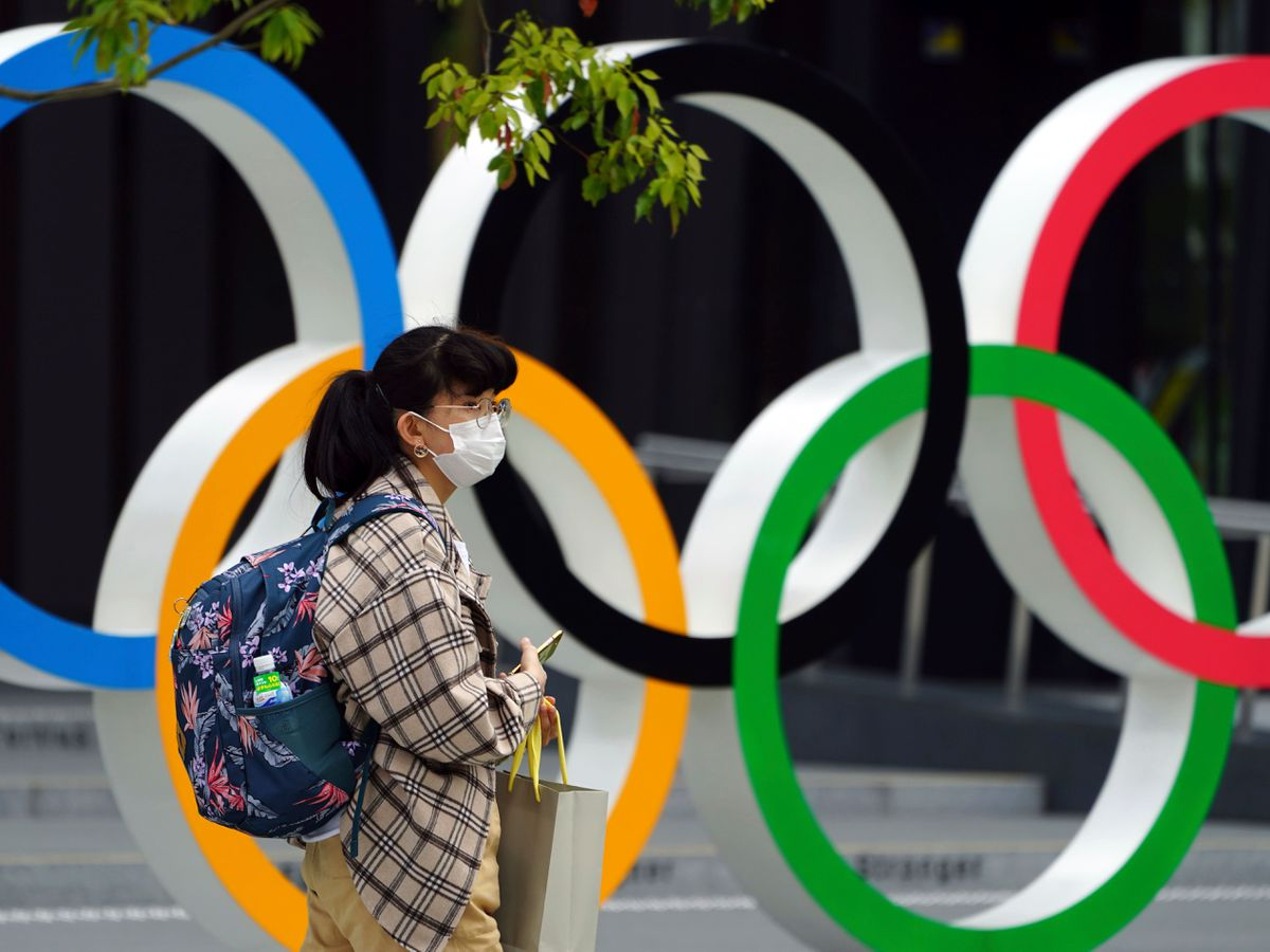 A woman wearing a protective mask walks in front of the Olympic Rings in Tokyo