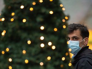 A man wearing a face mask passes Christmas lights outside a shop