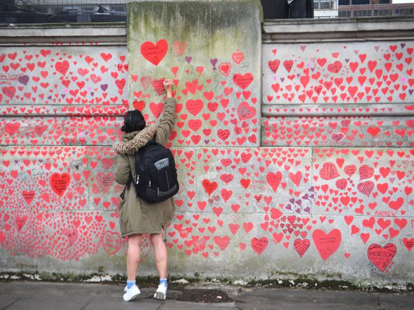 A woman writes in a heart on the National Covid Memorial Wall on the Embankment in London