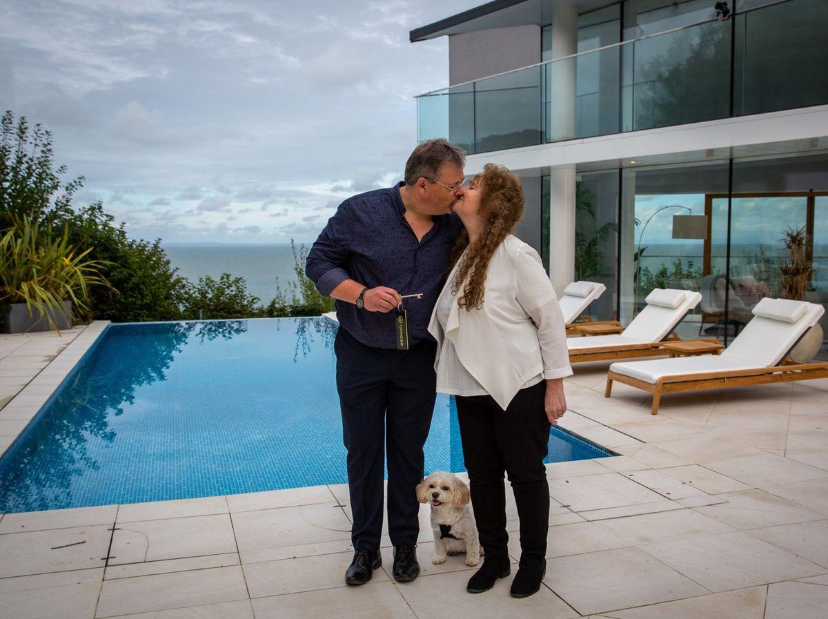 Glen and Debbie Elmy celebrate with their dog Bailey. Photo: Omaze