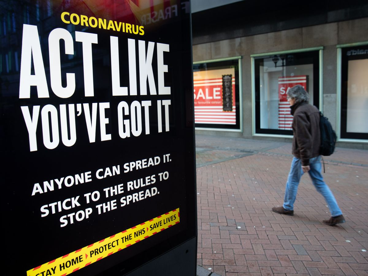A person passes an 'Act like you've got it' government coronavirus sign