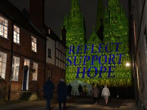 Lichfield Cathedral is illuminated with the words 'Reflect, Support, Hope'
