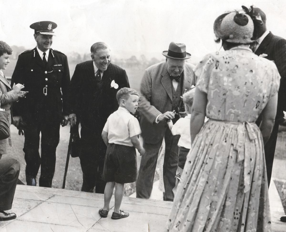 Four-year-old Richard Hill looks around after handing a cigar to Winston Churchill at Pendeford aerodrome in 1949