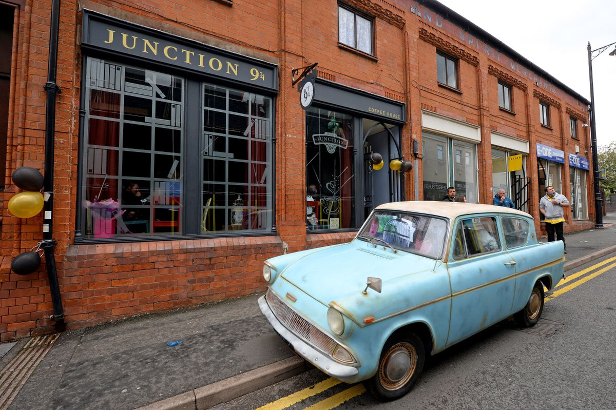A Ford Anglia was parked outside the cafe during the day