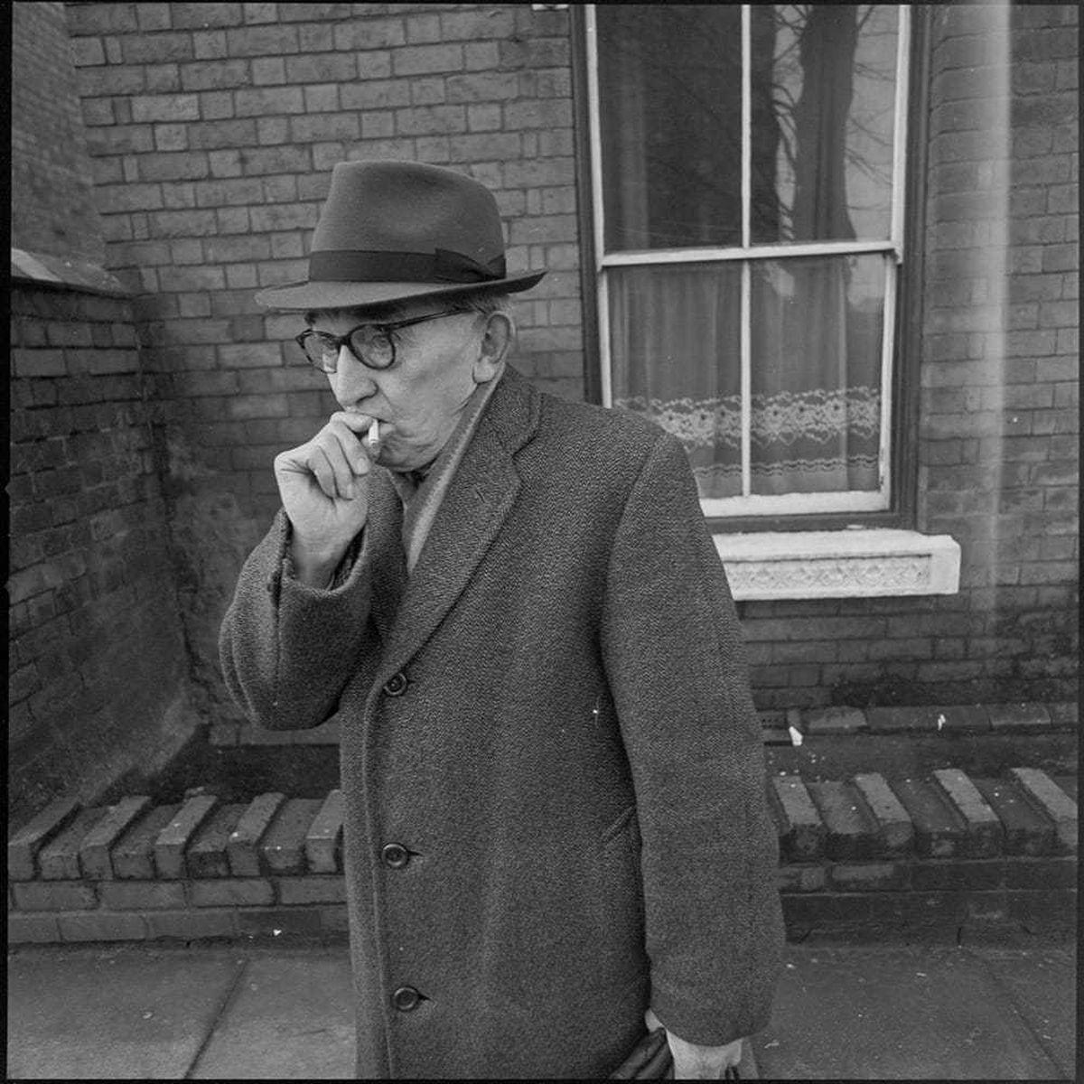An elderly man takes a drag on a cigarette