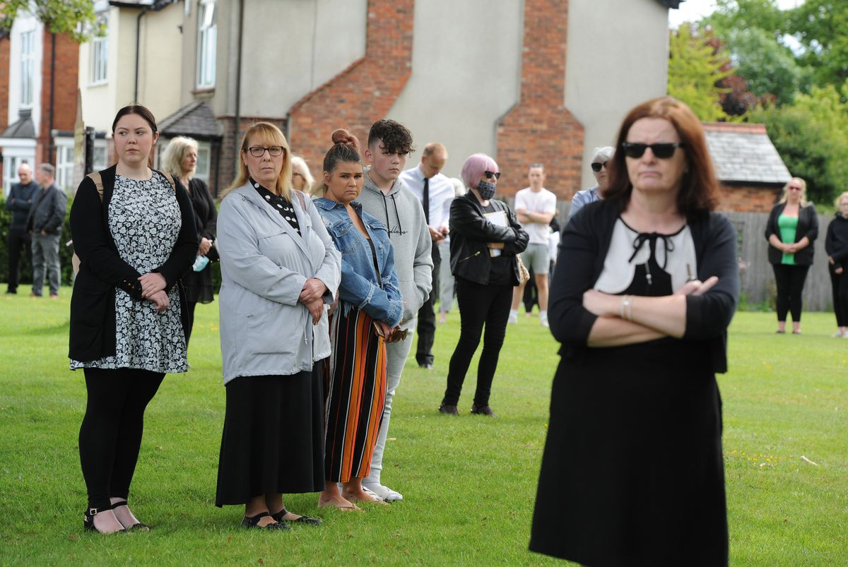 Mourners wait outside the church for the funeral procession to arrive