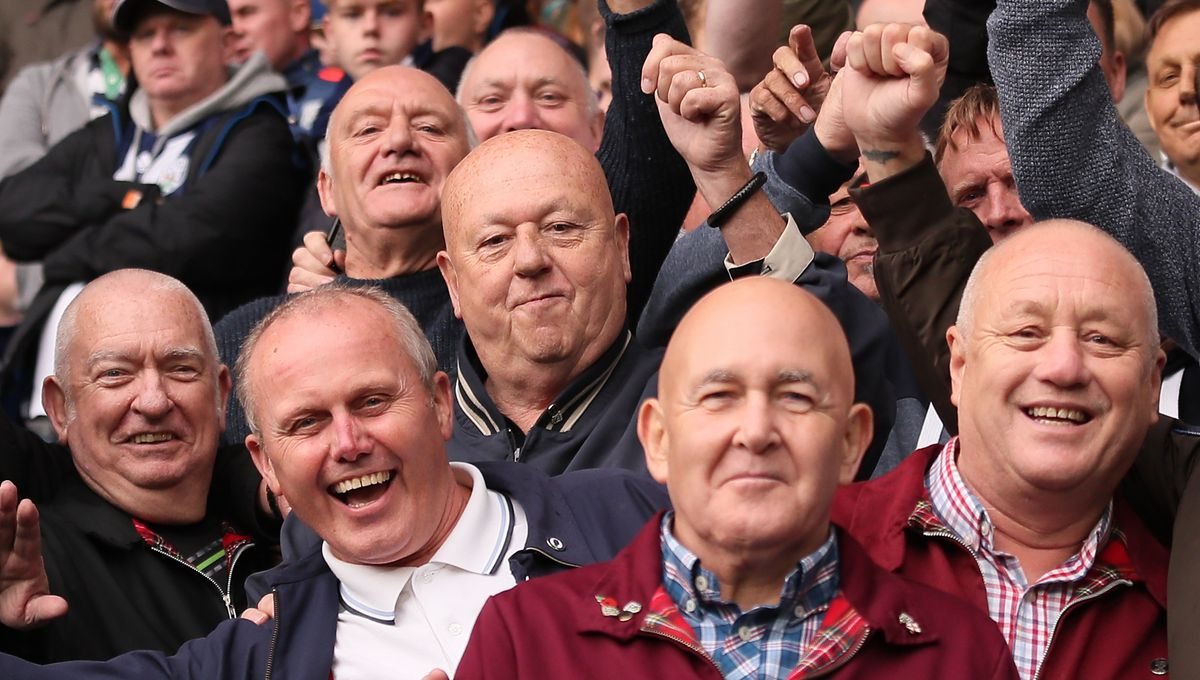 Keith White, centre, enjoys a reunion with Albion fans from Tipton at the home game against Watford last season. (AMA)