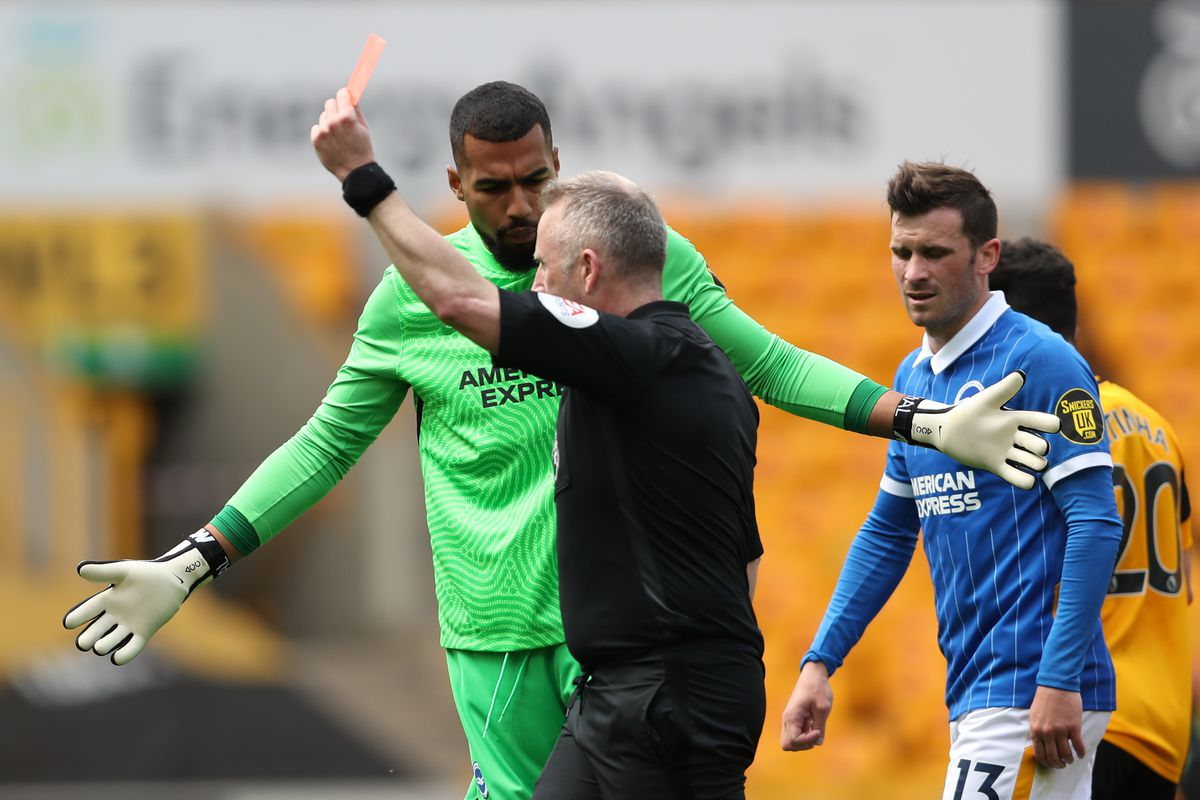 English Referee Jonathan Moss issues Lewis Dunk of Brighton and Hove Albion with a straight red card (AMA)