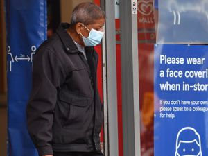 A shopper wearing a face mask leaves Tesco in Leicester city centre as non-essential shops in the city reopen following a local lockdown and face coverings become mandatory in shops and supermarkets in England. PA Photo. Picture date: Friday July 24, 2020. See PA story HEALTH Coronavirus. Photo credit should read: Jacob King/PA Wire.