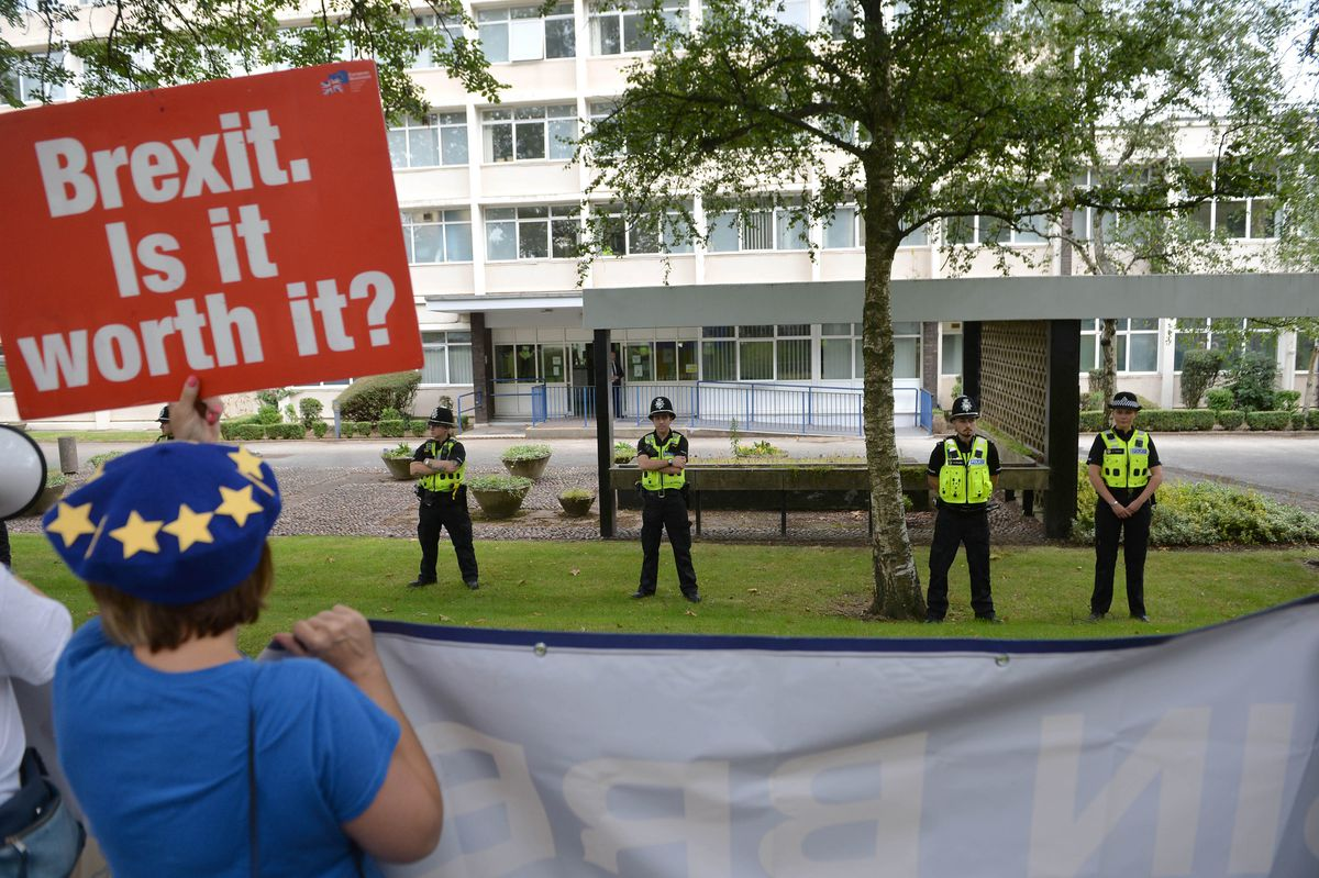 Police officers watched protesters as Prime Minister Boris Johnson arrived at West Midlands Police Learning and Development Centre in Birmingham on Friday