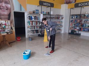 Senior store manager Mike Evans cleaning up the Compton Care store after the damage