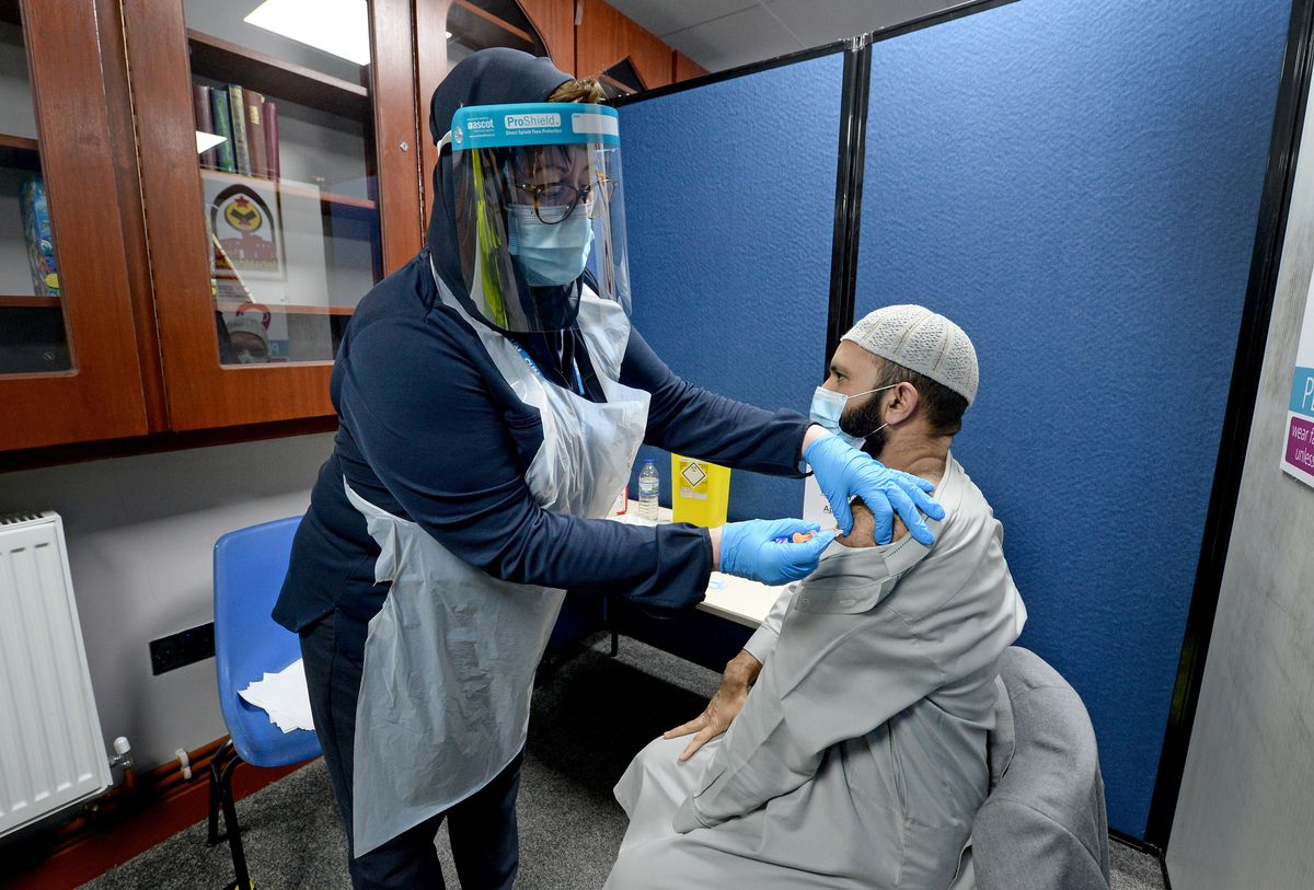 Imam of the mosque Muhammad Saeed arrives for his vaccination