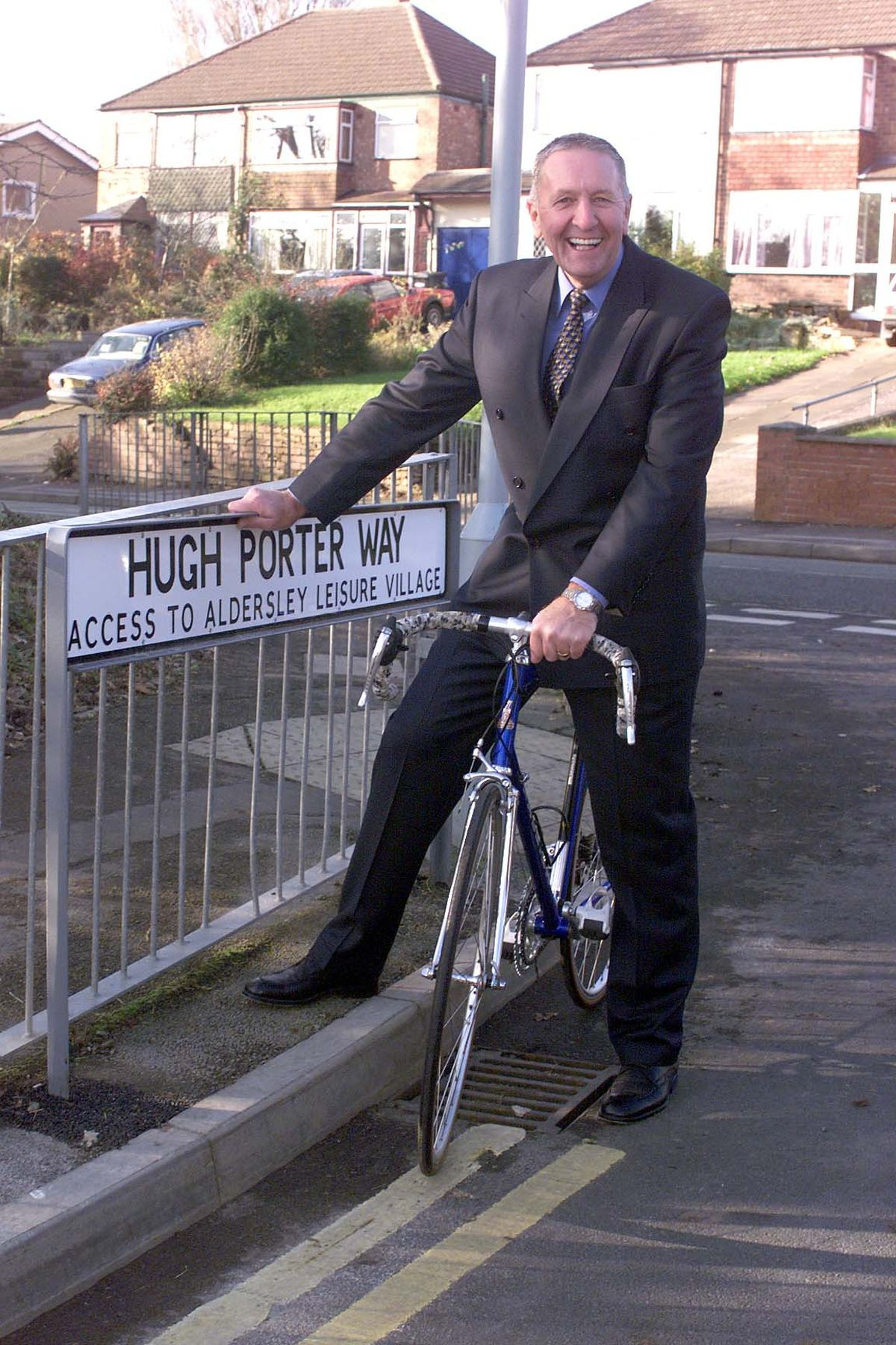 Ex-racing cyclist Hugh Porter poses with the road sign named after him on the road which leads to Aldersley Leisure Village.