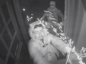 A man is captured on CCTV throwing a firework while another man behind him prepares to throw a traffic cone