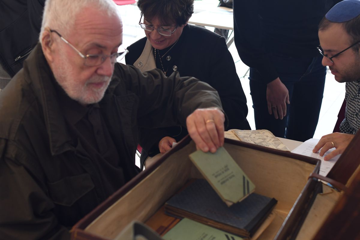Mr Rubin looks through the artefacts in his sister's suitcase. [credit Yad Vashem Archives]