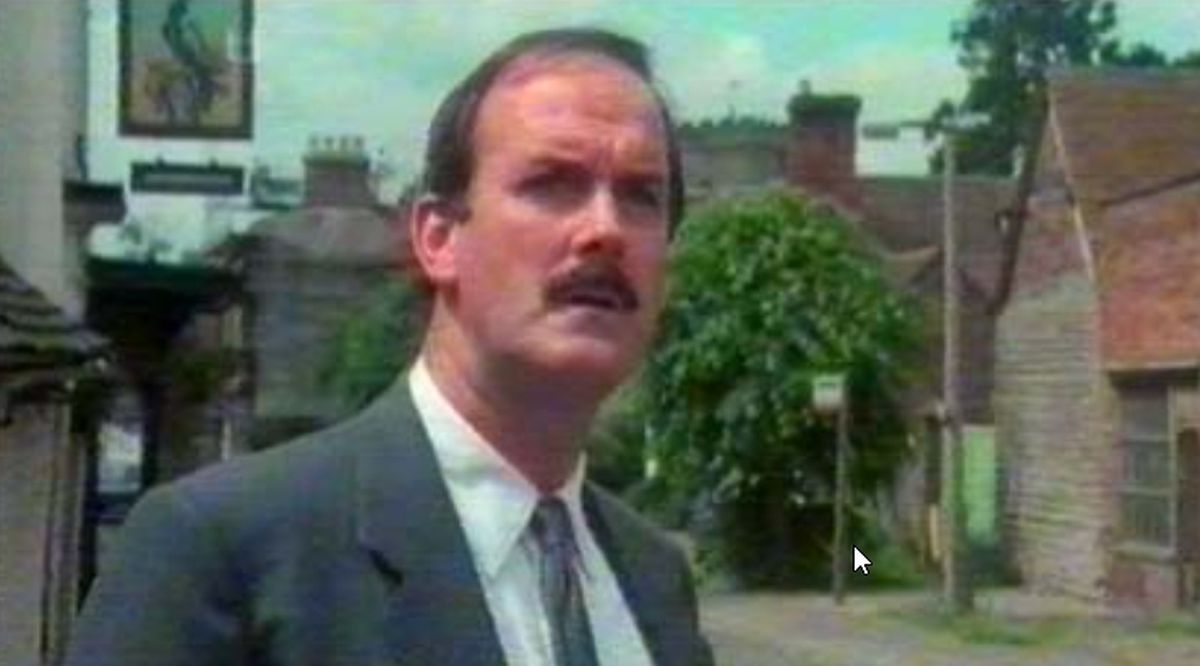 "John Cleese outside the Raven Hotel in Much Wenlock in the movie ""Clockwise."""