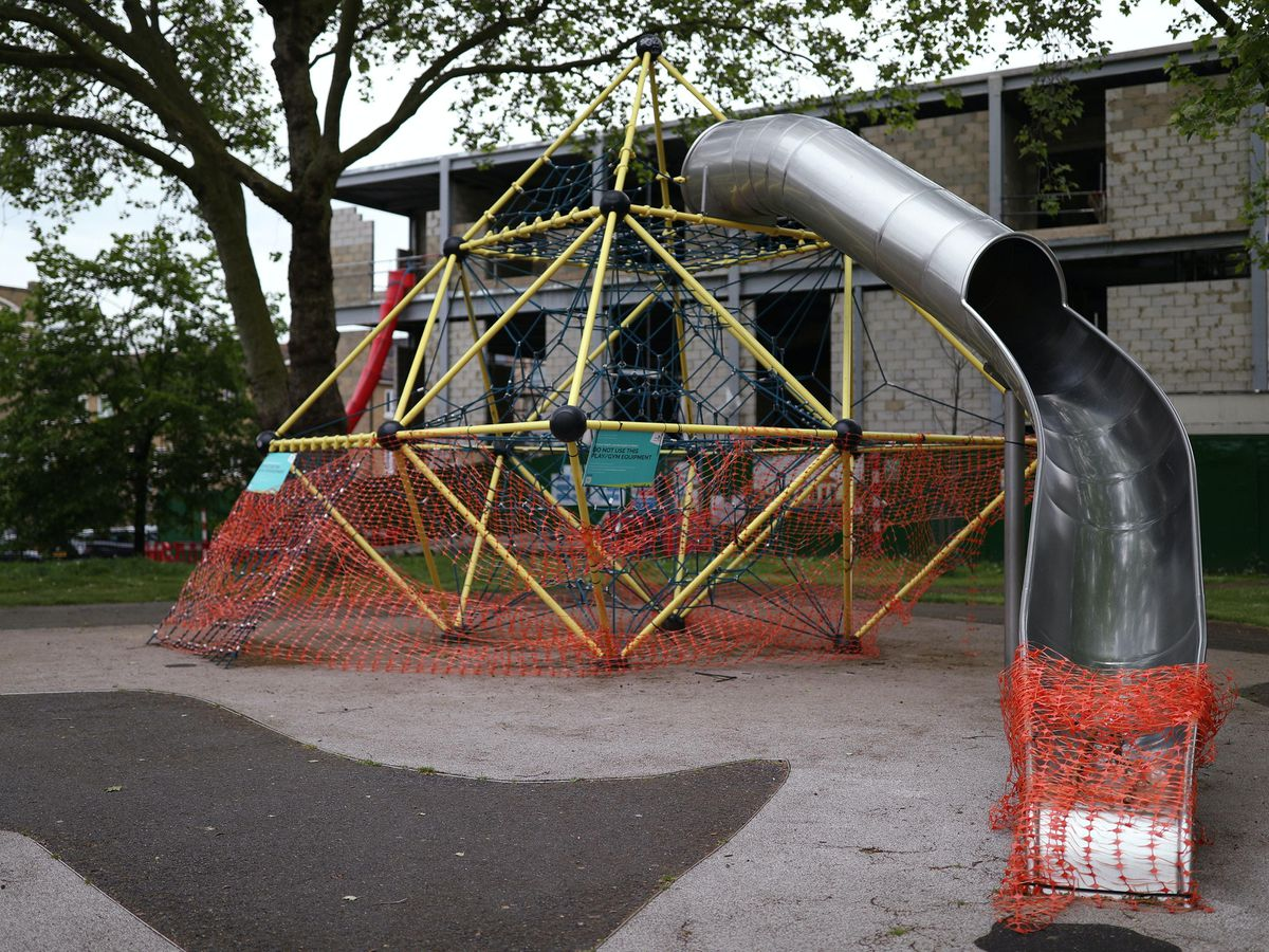 Activity equipment in the children's playground area of a park in London is closed off (Yui Mok/PA)